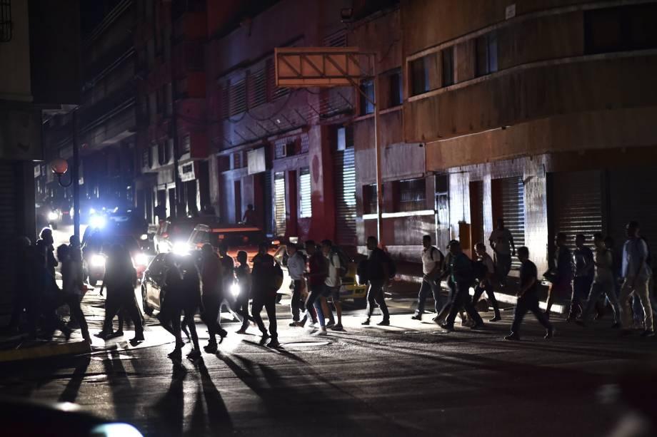 """Pessoas atravessam uma rua durante um corte de energia em Caracas. O governo de Nicolás Maduro aponta """"sabotagem"""" contra a principal represa de energia elétrica no país - 07/03/2019"""