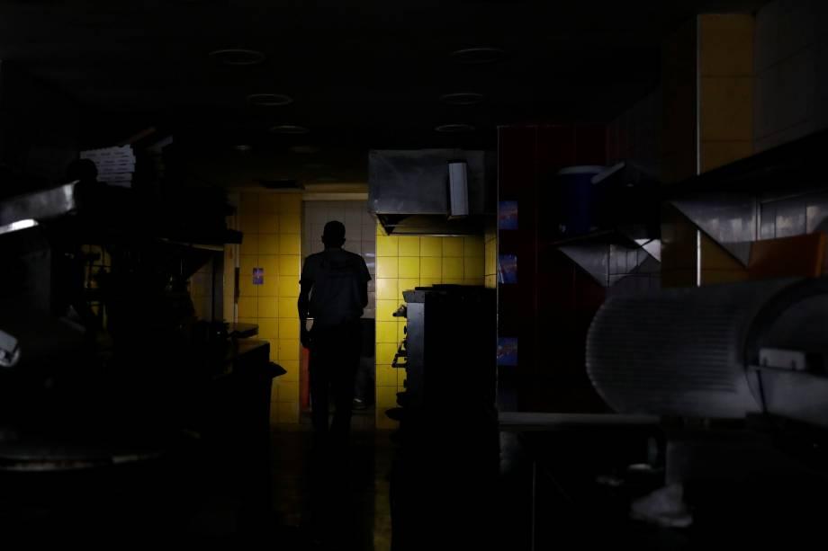 Homem usa o celular para iluminar a cozinha de um restaurante durante blecaute em Caracas, na Venezuela - 07/03/2019