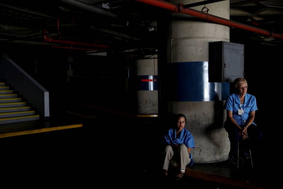 Trabalhadores esperam o retorno da energia elétrica em uma garagem durante um apagão em Caracas, na Venezuela - 25/03/2019