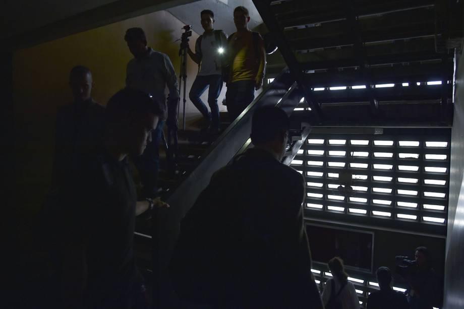Pessoas descem as escadas da Assembléia Nacional da Venezuela para evacuação do prédio após um apagão - 25/03/2019