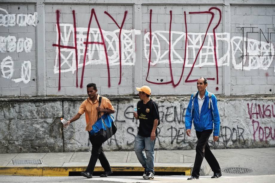 Pedestres caminham próximos de grafite com os dizeres 'Há luz?', durante novo apagão em Caracas, capital da Venezuela - 26/03/2019