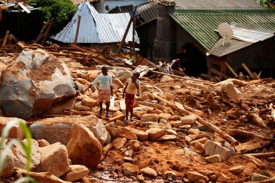 Crianças carregam galões de água entre escombros, após a passagem do ciclone Idai, na região de Chimanimani, fronteira entre o  Moçambique e o Zimbábue - 22/03/2019