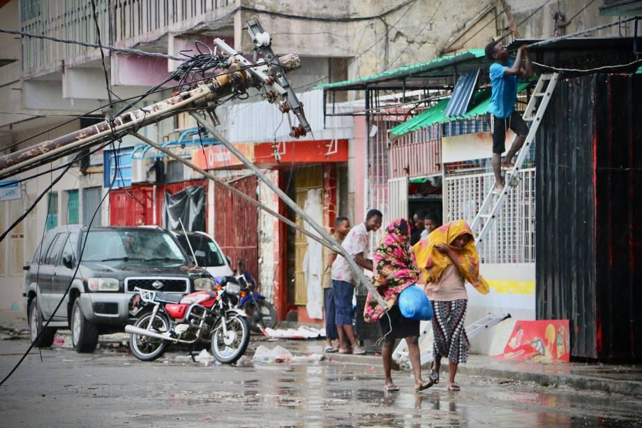 Moradores se protegem da chuva após a passagem do ciclone Idai na Beira, em Moçambique - 17/03/2019