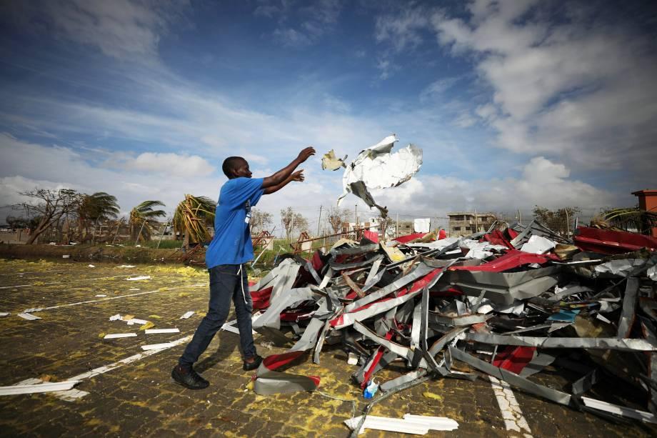 Homem empilha pedaços de metal arrancados de edifícios após a passagem do ciclone Idai na cidade de Beira, em Moçambique - 23/03/2019