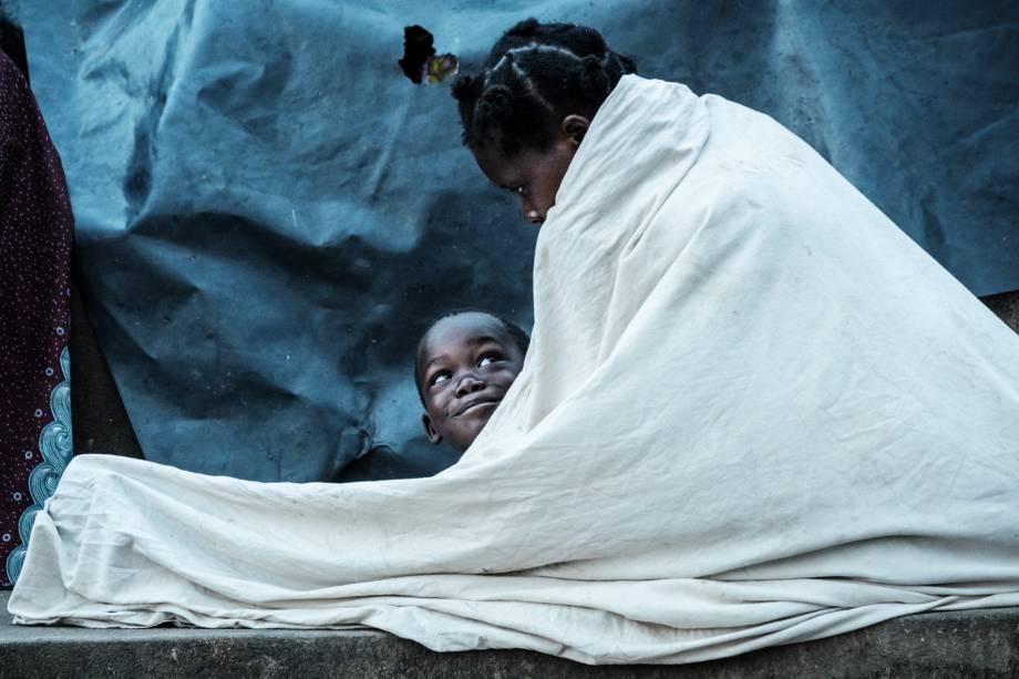 Maria Armando, 30, e seu filho Fernando Emmanuel, 5, se abrigam sob uma arquibancada em Buzi, Moçambique - 23/03/2019