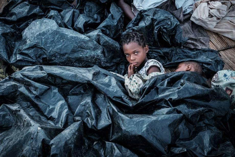 Enia Joaquin Luis, 11, acorda ao lado de sua irmã Luisa, 6, sob lençóis de plástico, para se proteger da chuva, em Beira Moçambique - 23/03/2019