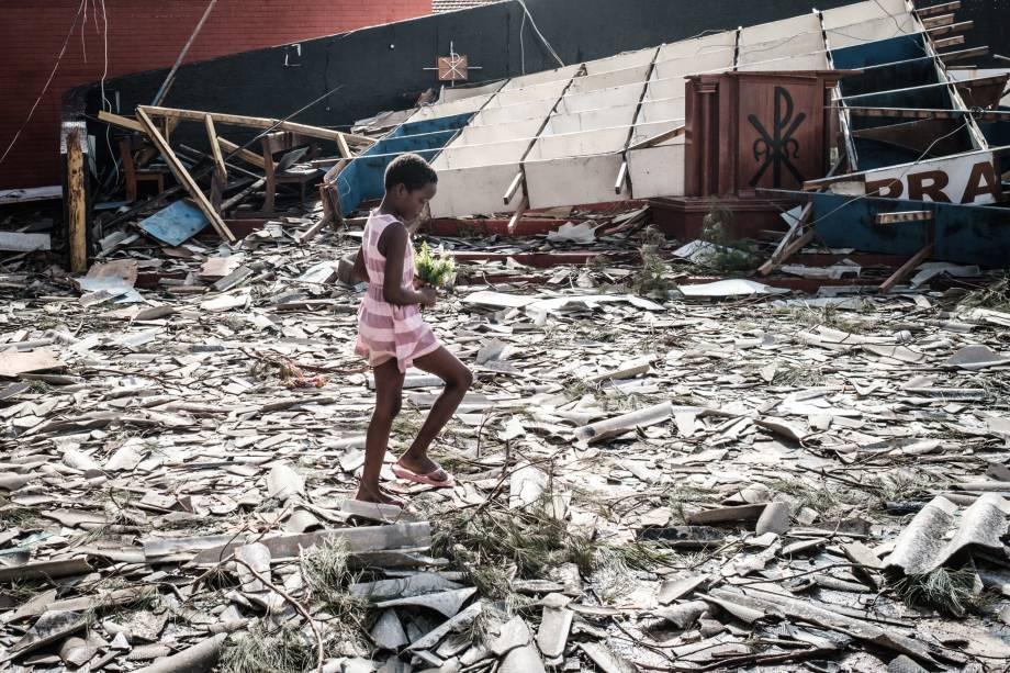 Menina recolhe flores artificiais dos escombros de um edifício destruído pelo ciclone Idai na Igreja Católica do Sagrado Coração, em Beira, Moçambique - 24/03/2019