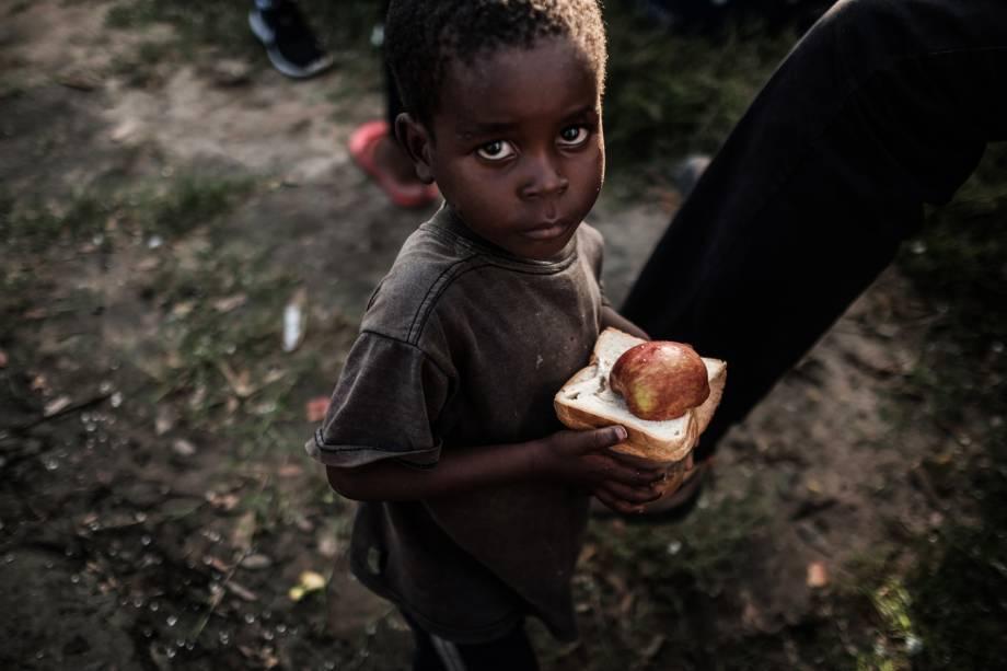 Garoto recebe alimentos em um centro de distribuição de um supermercado em Dondo, cerca de 35 km ao norte de Beira, cidade que ficou destruída após passagem do ciclone Idai em Moçambique - 27/03/2019