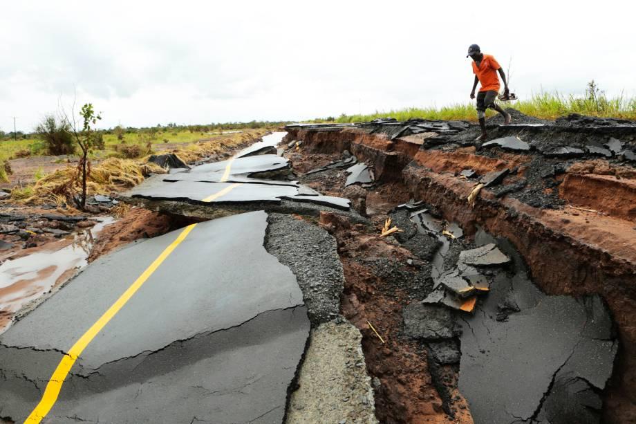 Homem atravessa estrada destruída após a passagem do ciclone Idai, na região de Nhamatanda, em Moçambique - 23/03/2019