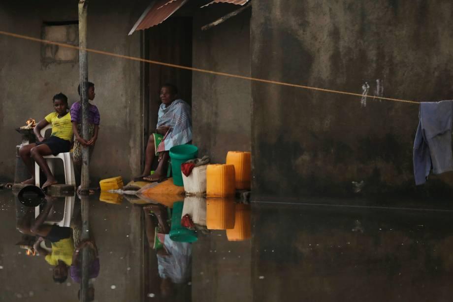 Família fica em sua casa cercada por água em uma aldeia a 40 quilômetros da cidade de Beira, Moçambique - 26/03/2019