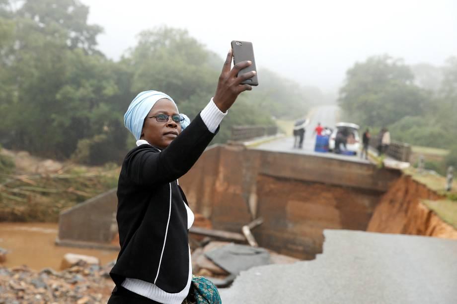 Mulher tira selfie junto de destroços de ponte que atravessa o rio Umvumvu em Chimanimani, Zimbábue - 18/03/2019