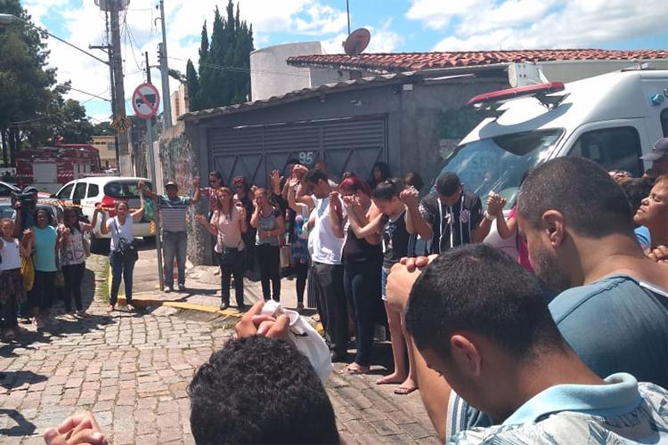 Familiares, alunos e vizinhos fazem oração em frente à Escola Estadual Raul Brasil, horas depois do ataque