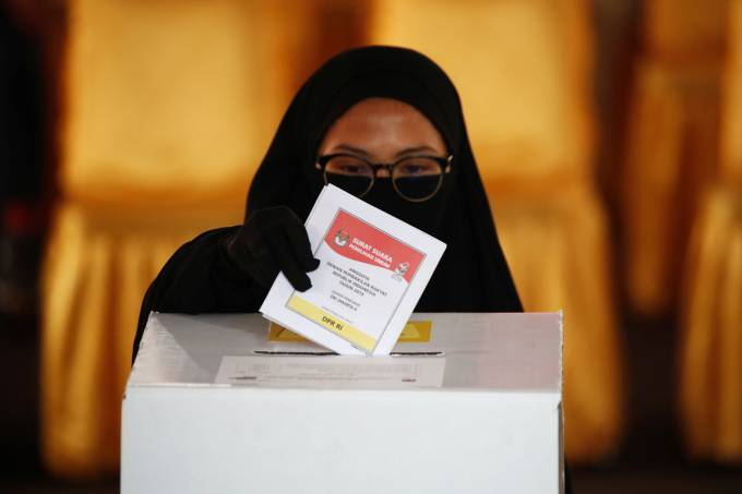 A voter casts her ballot during elections in Jakarta, Indonesia