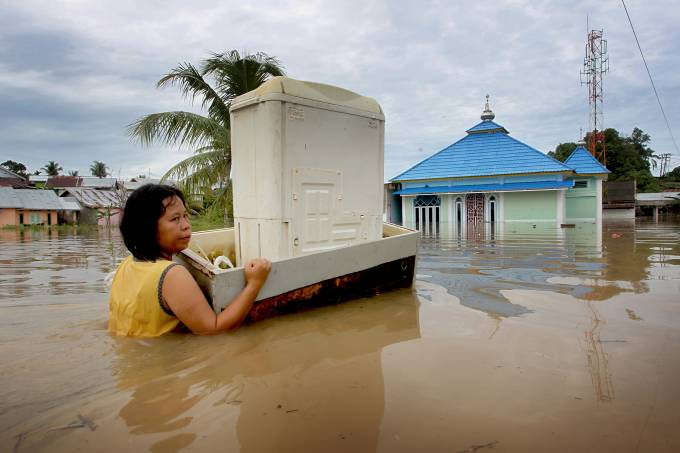 A woman carries her belongings with a raft through the flood in Bengkulu