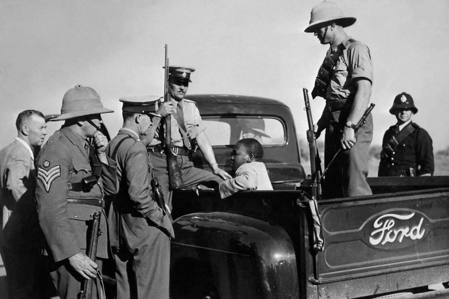 Homem negro é detido por policiais na cidade de East London, localizada na África do Sul - 01/10/1952