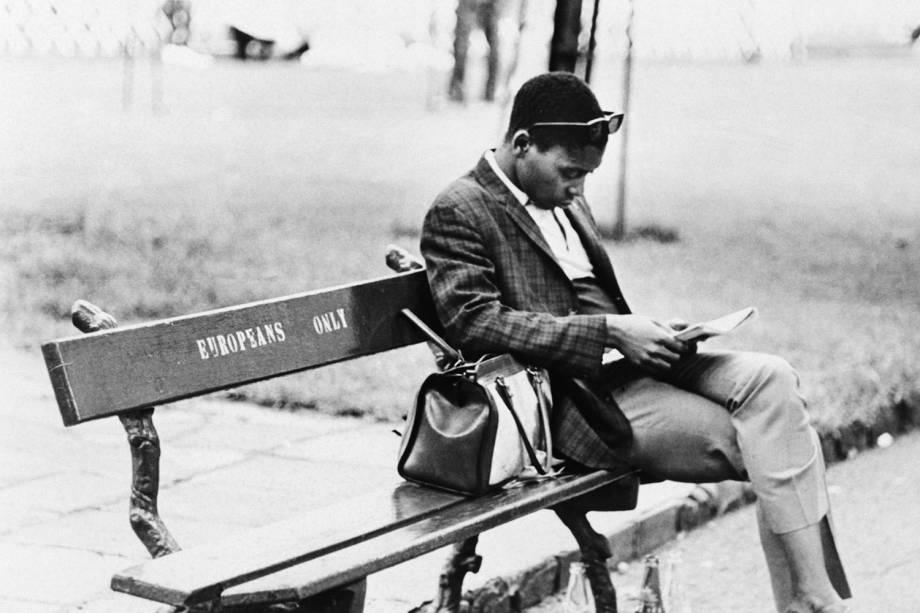 Homem negro senta em banco com os dizeres 'Europeus apenas', em um parque da África do Sul -  02/05/1970