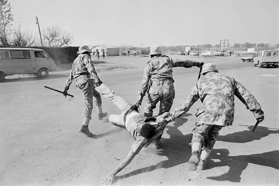 Policiais carregam manifestante anti-apartheid, durante protesto realizado em Soweto, na África do Sul - 15/06/1980