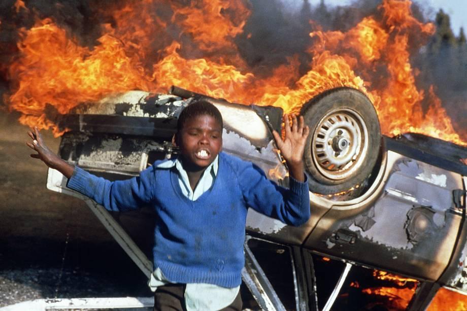 Garoto sul-africano é visto próximo de carro incendiado durante protestos realizados em Duduza, na África do Sul - 10/07/1985