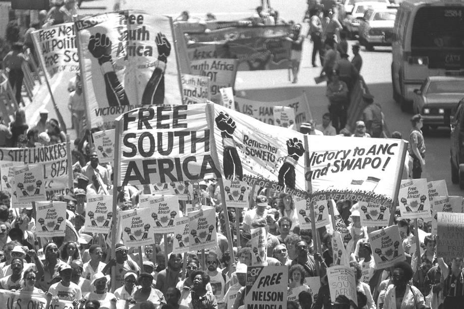 Manifestantes exibem faixas e cartazes durante protesto contra as políticas raciais implantadas durante o Apartheid, na África do Sul - 14/06/1986