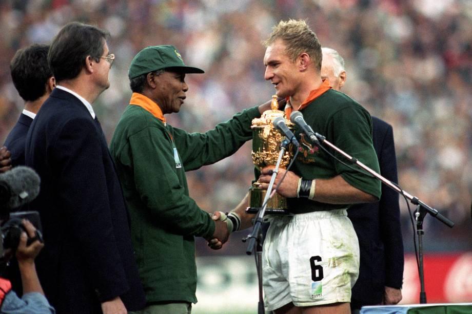 Francois Pienaar, então jogador de rúgbi sul-africano, recebe troféu do líder do país, Nelson Mandela, após a final do campeonato realizado no Estádio Ellis Park, localizado em Joanesburgo - 24/06/1995
