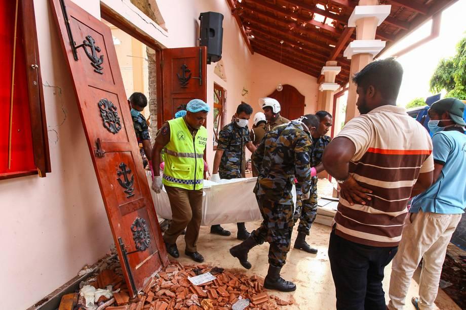 Cingaleses carregam o corpo de uma vítima para fora da Igreja de São Sebastião após uma explosão em Negombo, ao norte de Colombo, Sri Lanka - 21/04/2019
