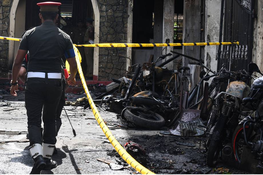 Policial passa ao lado de motocicletas destruídas do lado de fora da Igreja Zion, após uma explosão em Batticaloa, no leste do Sri Lanka - 21/04/2019