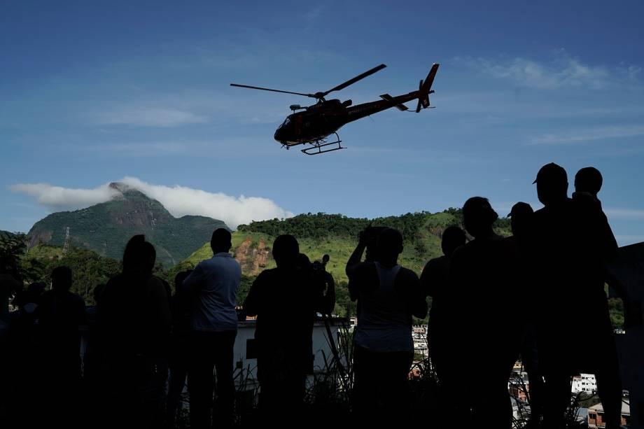 Moradores observam helicóptero que leva vítima de desabamento de prédio na comunidade de Muzema, no Rio de Janeiro - 12/04/2019