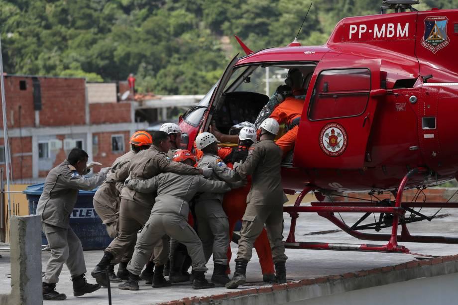 Homem em uma maca é carregado para um helicóptero no local do desabamento de dois prédios na comunidade da Muzema, Rio de Janeiro - 12/04/2019