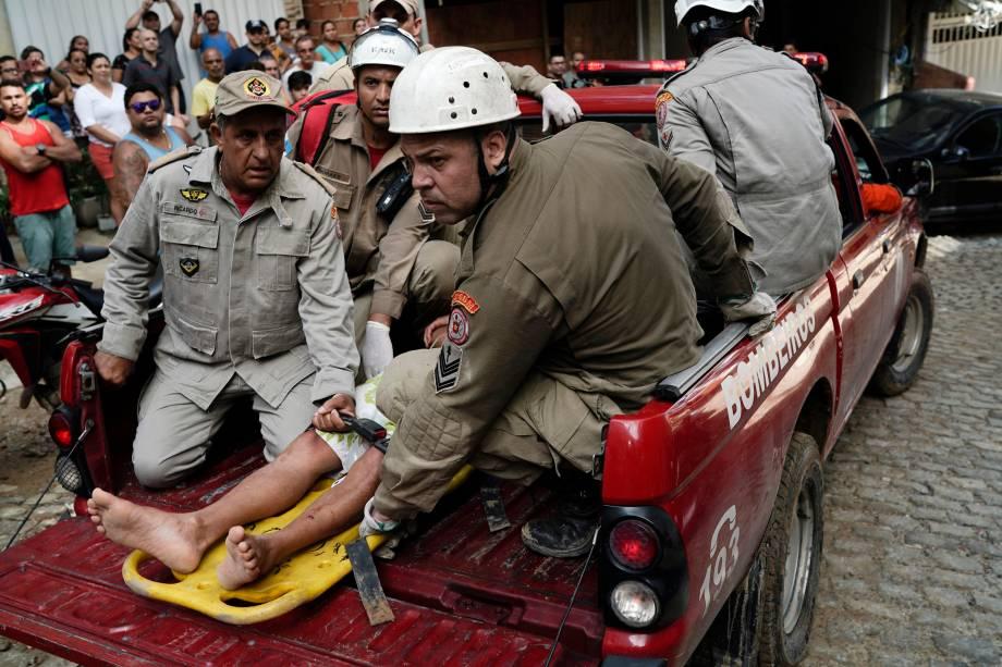 Bombeiros carregam uma pessoa ferida resgatada dos escombros de dois prédios que desmoronaram na comunidade da Muzema, no Rio de Janeiro - 12/04/2019