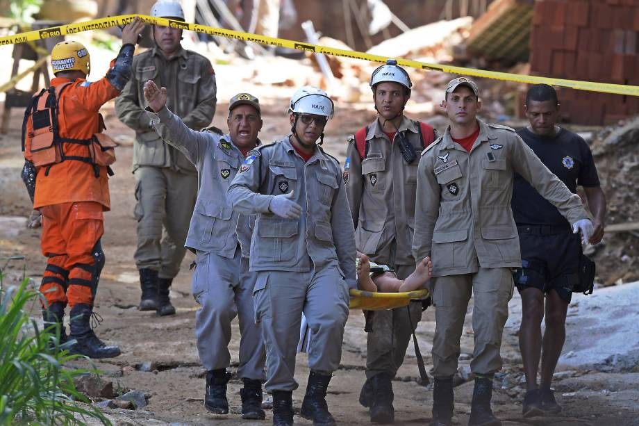 Equipes de resgate carregam uma pessoa ferida depois que dois prédios desabaram na comunidade da Muzema, Rio de Janeiro - 12/04/2019