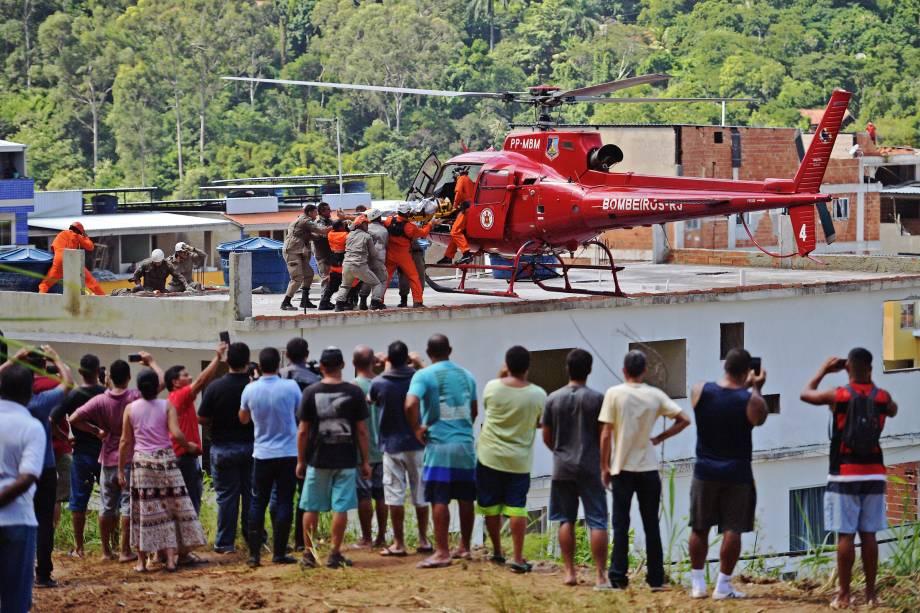 Pessoa ferida é levada para um helicóptero após ser retirada dos escombros de dois prédios que desabaram na comunidade de Muzema, Rio de Janeiro - 12/04/2019