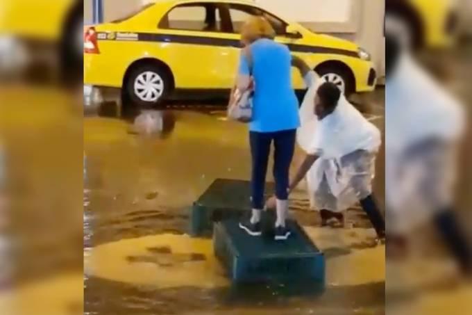 Homem ajuda uma mulher a atravessar uma rua alagada no Rio
