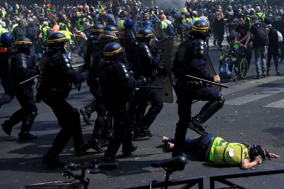 Um policial passa por cima de um manifestante durante a 23° manifestação consecutiva do movimentos dos Coletes Amarelos em Paris - 20/04/2019