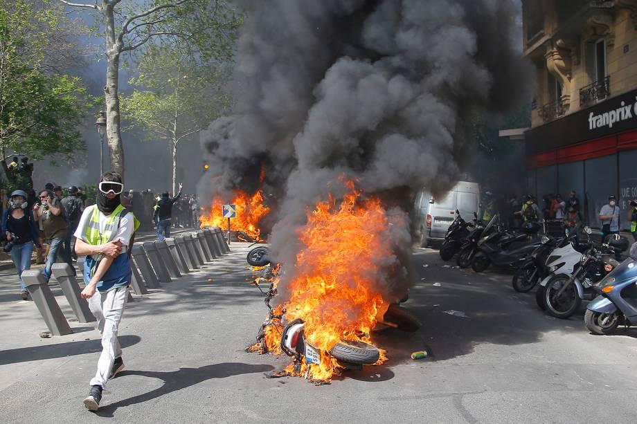 Manifestante de colete amarelo passa ao lado de motocicletas em chamas durante um protesto em Paris, na França - 20/04/2019