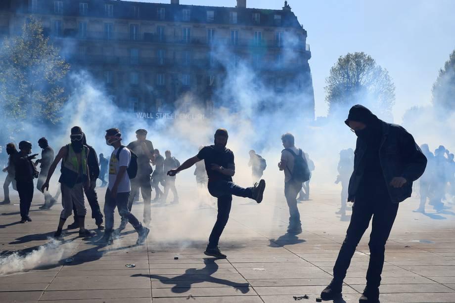 Manifestante chuta uma bomba de gás lacrimogênio disparada pela polícia durante o 23° protesto consecutivo aos sábados em Paris, na França - 20/04/2019