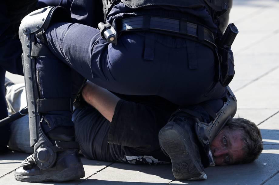 Policial detém um manifestante durante um protesto dos Coletes Amarelos em Paris, na França - 20/04/2019