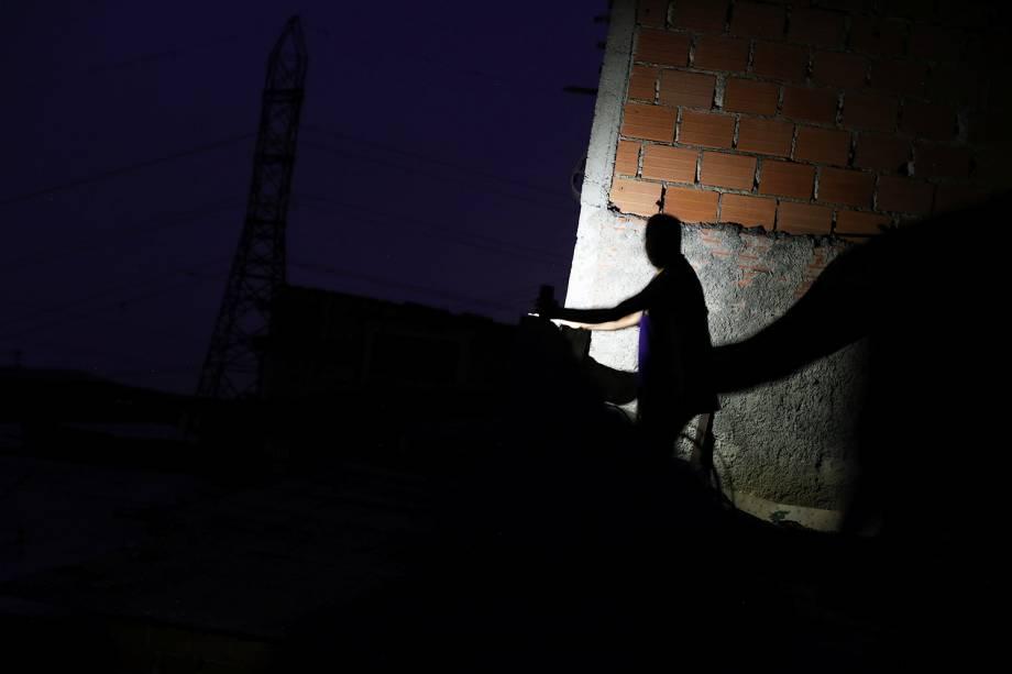 Homem utiliza lanterna de celular em bairro de Caracas, capital da Venezuela, durante apagão que atinge o país - 27/03/2019