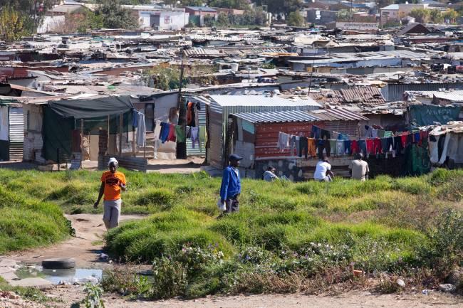 Moradores caminham entre os barracos da favela de Diepsloot, um dos bairros mais pobres de Joanesburgo na África do Sul