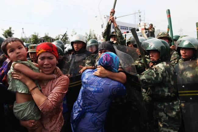 Policiais chineses empurram mulheres da etnia uigur durante protesto em Urumqi, capital da região autônoma de Xinjiang – 07/07/2009