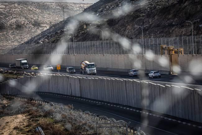 Veículos trafegam na polêmica rodovia da Cisjordânia, dividida por um grande muro de concreto segregando o tráfego israelense e palestino