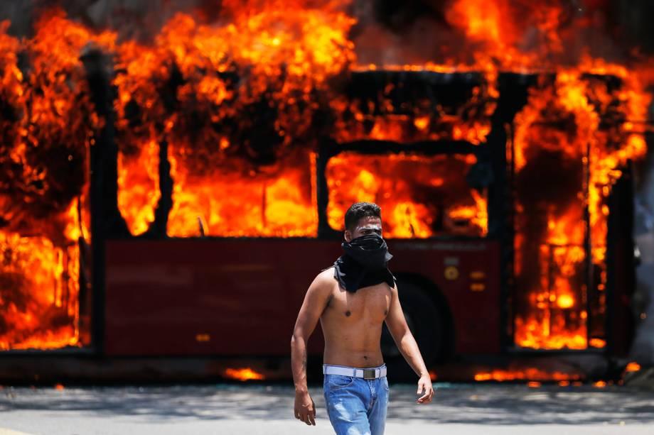Manifestante da oposição caminha próximo de ônibus incendiado durante protestos em Caracas, capital da Venezuela - 30/04/2019