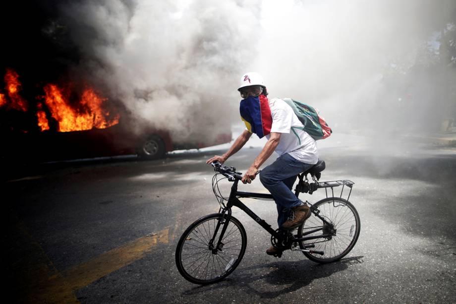 """Manifestante da oposição pedala bicicleta próximo de ônibus incendiado, nos arredores da base aérea Generalisimo Francisco de Miranda """"La Carlota"""", em Caracas, capital da Venezuela - 30/04/2019"""