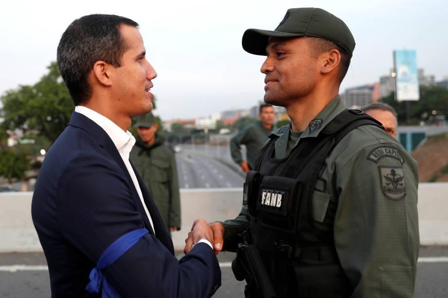 """O presidente autoproclamado da Venezuela, Juan Guaidó, cumprimenta um membro das Força Armada Nacional Bolivariana perto da Base Aérea """"La Carlota"""", em Caracas - 30/04/2019"""