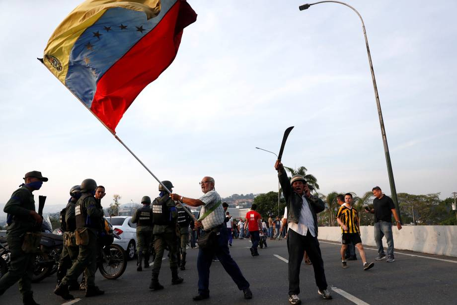 """Manifestante de oposição agita uma bandeira venezuelana perto da Base Aérea """"La Carlota"""", em Caracas - 30/01/2019"""