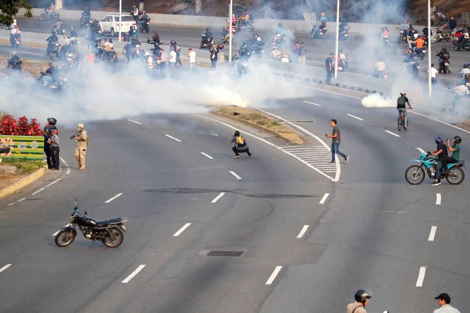 """Pessoas reagem ao gás lacrimogêneo durante confrontos nos arredores da base aérea """"La Carlota"""", em Caracas, Venezuela - 30/04/2019"""