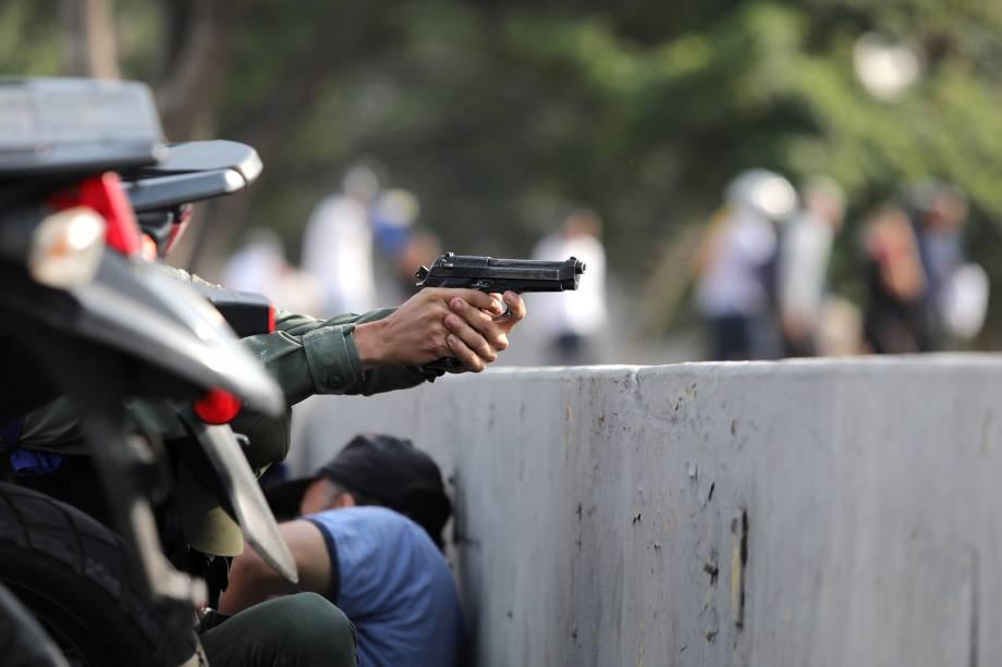 """Militar aponta uma arma durante manifestações nos arredores da Base Aérea """"La Carlota"""", em Caracas, na Venezuela - 30/04/2019"""