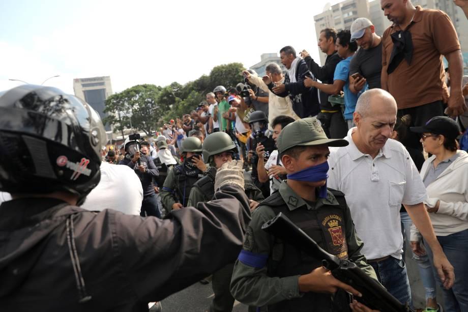 """Pessoas reagem à presença de militares nos arredores da Base Aérea """"La Carlota"""", em Caracas, na Venezuela - 30/04/2019"""