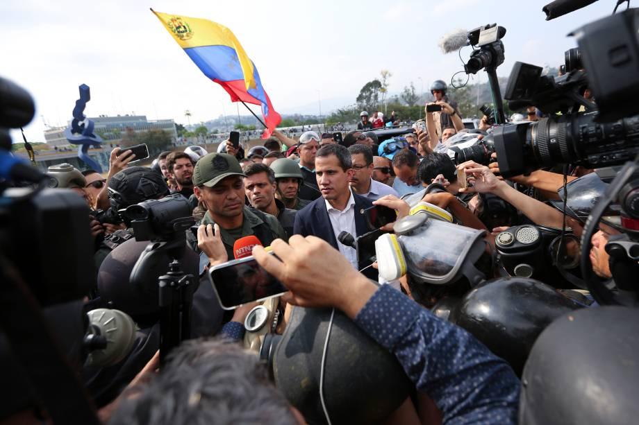 O líder da oposição venezuelana e autoproclamado presidente Juan Guaidó, aparece ao lado de um oficial militar não identificado enquanto é cercado pela imprensa e apoiadores do lado de fora da base aérea de La Carlota em Caracas - 30/04/2019