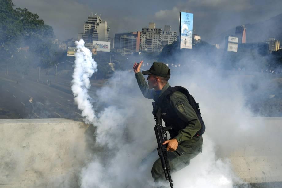 Membro da Guarda Nacional Bolivariana apoiador do líder de oposição Juan Guaidó lança uma bomba de gás lacrimogêneo durante confronto com forças leais ao governo do presidente Nicolas Maduro em frente à base militar de La Carlota em Caracas - 30/04/2019