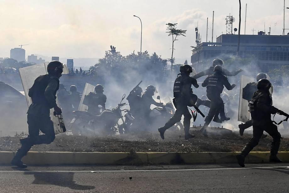Membros da Guarda Nacional Bolivariana, leais ao presidente Nicolás Maduro, correm sob uma nuvem de gás lacrimogêneo durante confronto com apoiadores de Juan Guaidó em frente à base militar de La Carlota, em Caracas - 30/04/2019